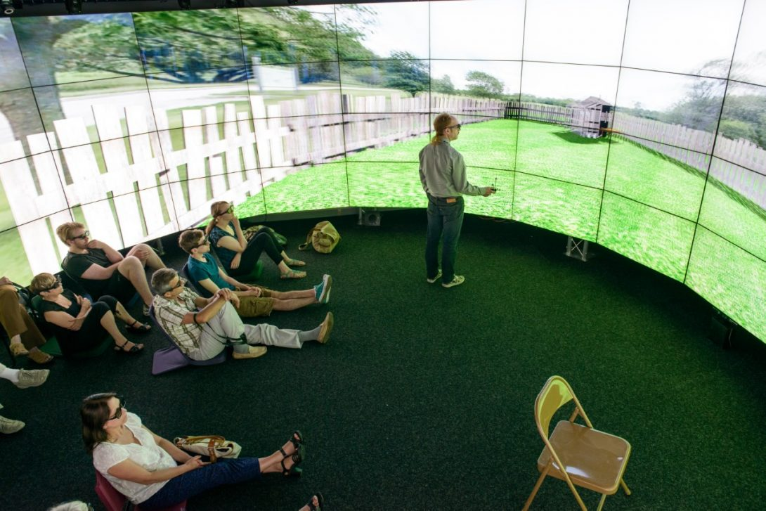 audience immersed in a story at UIC's CAVE2™, a virtual reality environment
