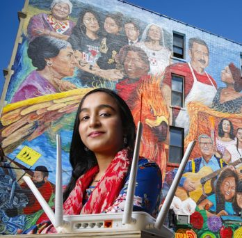 Afifa Nadeem in front of a mural in Pilsen by the artist Pablo Serrano