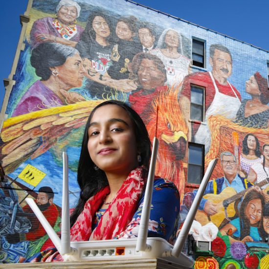 student with an Internet router in front of a colorful mural in the Chicago neighborhood of Pilsen